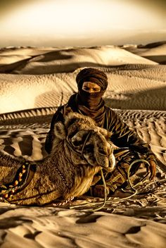 Maroc with his Camel at the lonely Desert.