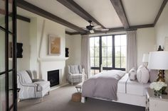 While simple in its tones, this master bedroom has tons of visual impact! The fireplace feels warm and inviting, and white and gray linens keep the space feeling fresh and clean. Adding to its charm, the room features an exposed beam ceiling, beautiful windows and comfy armchairs around the fireplace.