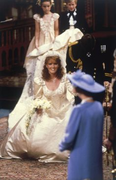 A smiling Lady Sarah Ferguson, Duchess of York, curtseys to Queen Elizabeth II, her mother-in-law following her marriage to Prince Andrew, Duke of York at Westminster Abbey on 23 July 1986