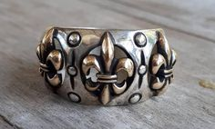 gold fleur de lis On sterling silver ring Beautifully ornate Rounded top Gold pieces are solid weights 13 gms Sits Beautiful two tone ring If your size is not listed please convo me for a quote Also available in all silver Gold And Silver Rings, Silver Wedding Rings, Sterling Silver Rings, Wedding Bands, Ace Ring, Celtic Rings, Dress Rings, Colored Diamonds, Solid Gold