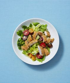 Oven-Fried Chicken With Lemony Romaine Salad | RealSimple.com. Think of this salad as a lightened-up Caesar, topped with crispy baked chicken and sprinkled with grated Parmesan. You'll love the simplicity of the homemade lemon vinaigrette.