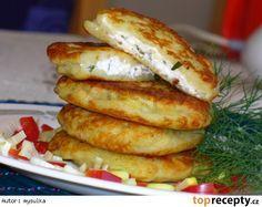 Bramborové placičky se sýrovo bylinkovou náplní-Oloupané brambory nastrouháme jako na bramborák, slijeme přebytečnou vodu, přidáme vejce, mouku, osolíme, opepříme a umícháme. Sýry a bylinky promícháme a osolíme a opepříme podle chuti. Na lívanečníku, nebo pánvi rozehřejeme trochu oleje, vložíme bramborové těsto, na něj dáme lžičkou náplň, opatrně rozetřeme a přikryjeme další vrstvou těsta. Pečeme z obou stran dozlatova.