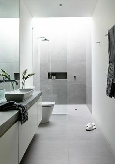SOUTHERN WING BATHROOM. Grey floor tile that continues up the wall of the shower. White tiling to ceiling throughout. White cabinetry (shaker profile) with grey countertop. Black window frames. Black tapware.