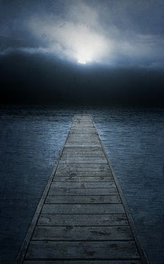 A dock over the water with moon partly hidden behind clouds