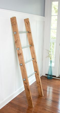 Industrial decor meets rustic farmhouse with a twist. This wooden ladder has a reclaimed wood appearance yet it looks sophisticated and sleek