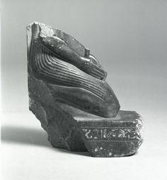 Lower part of a schist kneeling figure wearing a shendyt kilt offering a figure of a standing deity; inscribed base and dorsal pillar (cracked), Hieroglyphs name Bakenkhons.