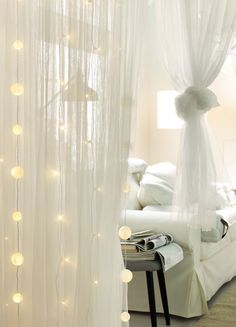 String Lights Hanging From The Ceiling Infront Of Thin Muslin Curtains