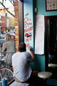 Hand Painted Sign by Sean Barton. The cell phone booth is still outside.