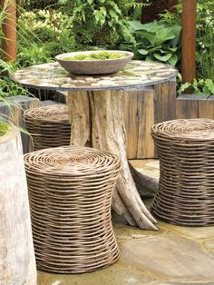 Basket weave stools and a tree trunk table blend seamlessly with a rustic-style garden.