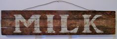 """Antiqued Milk DIY Sign ~Sarah Schrenk - SarahSCraftyCreations~ used 2 1/2""""wx5 ft long pc of molding, cut down to 3 18"""" long pcs. I cut 2- 5"""" pcs glued on back to hold all 3 pieces together. W/a meat mallet, I LIGHTLY tenderized wood. I Made a stencil-(Large font letters online, Wax paper, craft knife, spray adhesive, white paint). Used a kitchen sponge (cut a 3"""" piece), sponged on paint. Then I lightly sanded over paint. The hanger-made w/gardening wire. Simple for a country look."""