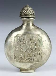 China, 19th C., silver snuff bottle of circular form, decorated with a floral carved scene, with stopper. Height 2 1/4 in.