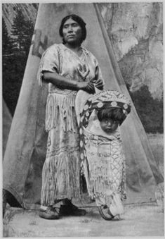 """Yosemite mother & child-Cradles, of openwork basketry were woven and then covered with deer skin for carrying the papoose. The Yosemite Indians referred to this device as a """"hickey"""".   Special ornately designed baskets were woven specifically for use in wedding and dance ceremonies."""