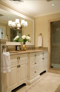 Cream cabinets and large framed mirror, pretty hardware as well