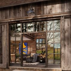 Fischbach reclaimed barn. Designer Jenny Fischbach added contemporary glass panels to replace the barn's original alley doors, allowing plenty of natural light to stream into the main living area. #ModernFarmhouse