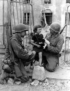 Two American soldiers attempt to cheer up a distraught child with a puppy. She was most likely separated from her family. (France, June-July 1944)