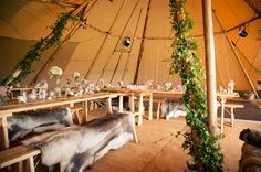 Wedding tepee - wood tables and benches with animal skin rugs.  Sorori_Tipi_Marquee weddings03