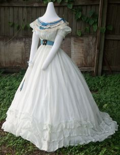 Muslin ballgown c.1865/6 shown with a bertha c.1865/6, belt with buckle c.1865 and mirrored fan c.1860s