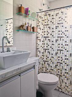 O banheiro da suíte é charmoso com sua cortina de plástico, descoberta em uma de nossas matérias. Na Telhanorte, custa R$ 7,90 (em várias estampas). Da mesma loja são as prateleiras de vidro (R$ 80 cada).