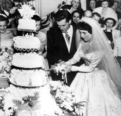1950: Elizabeth Taylor and her first husband Nicky Hilton cut the cake at their wedding reception