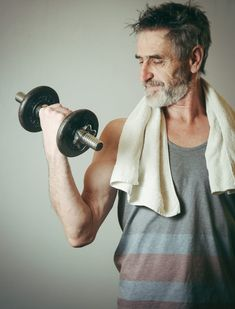 Senior man lifting weights on the grey background