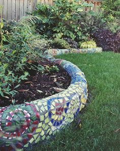 Colorful glass and tile are cut and combined into a swirling mosaic on this small curving wall set off by plants that accent the design.
