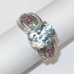 Silver ring with white gold finish. Blue topaz, garnet, zirconium, chrysolite Sold by Jewellry 133,00 $