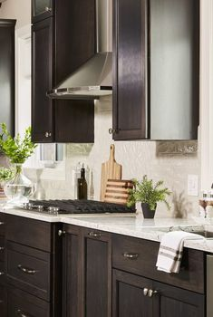 Dark stained cabinets with light quartz countertops and wavy subway tile backsplash.