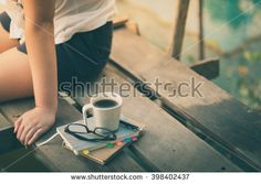 Notebooks, pen, glasses, and coffee cup are putting down on the wood bridge while young woman sitting beside them in morning time on weekend with instagram vintage filter effect