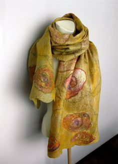 Hand felted scarf made with merino wool and lots of silk. Cobweb felt is lightweight, warm, and lacy, holes are part of the design. Approximate