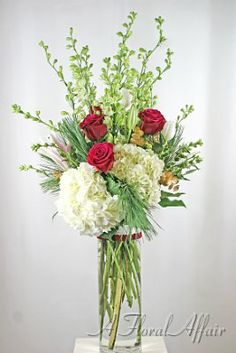 When you have limited table space, make a statement with heighth. White larkspur, hydrangea, tulips, stargazer lilies and red roses are dramatic on a buffet table. HD8054-Traditional Holiday Buffet Centerpiece Flowers by A Floral Affair - www.afloralaffair.com #ChristmasFlowers #HolidayArrangement
