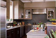 Les meubles en bois de cette cuisine sont peints dans une nuance de gris chaud et soutenu en finition satin,  les meubles hauts eux s'affichent dans une nuance de mordoré (que l'on retrouve souvent en association avec les gris foncés) et amène un effet lumière efficace.