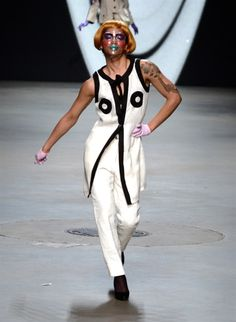 Colorful facial make-up and pastel purple gloves accentuate and harmonize superbly with the black and white top and bottom. The jaunty walk of the model adds up the vibrancy.