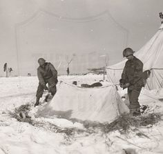 """""""Artillerymen with 4th Infantry Division in Luxembourg set up their camouflaged shelter tent in snow. Left to right: Cpl. Jimmie E. Smallwood, Ola, Georgia, and Pfc. Gordon A. Mitchell, of Spring City, Tennessee. 945th Field Artillery Battalion, Battery A, 4th Infantry Division. January 14, 1945. Photographed by T/4 F. Mastrosimone."""""""
