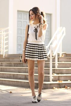 Preppy look in black and white wearing a cute bow shirt with pleated striped skirt. Also wearing black and white accessories with mini bag and oxfords.