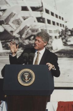 Commemorating the one-year anniversary of the 1994 Northridge earthquake, President Bill Clinton spoke at California State University, Northridge on January 17, 1995. President Clinton praised federal, state, and local agencies on their recovery efforts. He is shown at a podium bearing the Presidential Seal; behind him is a large black-and-white photograph of a parking structure that partially collapsed as a result of the quake. CSUN University Digital Archives.