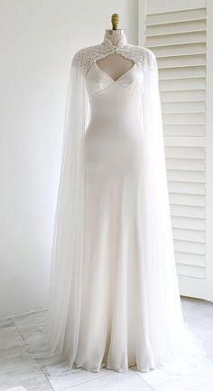 Floor-skimming tulle is adorned with embroidered lace appliqué along the shoulders and high neckline of this romantic long GALINA cape. It is the perfect modern alternative to the traditional veil! Dream Wedding Dresses, Bridal Dresses, Wedding Gowns, Wedding Dress Cape, Wedding Cape Veil, Long Cape Dress, Wedding Dress Collar, Boho Wedding, Mermaid Wedding