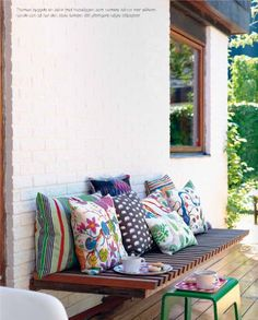 back porch bench with bright patterned pillows