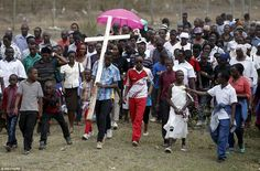 Making a stand: A Christian man carries a cross during Good Friday procession outside Nair...