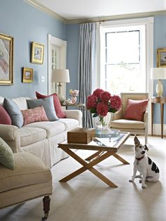 Pale blue walls warmed up with wood pieces and comfortable creamy upholstery. Bold magenta accessories add punch.