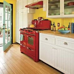 An energetic color scheme—yellow walls, red pendants, a citron ceiling, and lime green wainscoting—makes this remodeled kitchen as warm and welcoming as its 1940s stove.