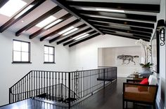 Second floor hallway in a Spanish Revival home with exposed painted black beams. love the wolf!