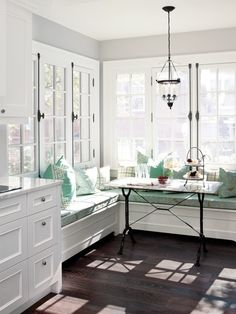Built in bench seating under a window in a bright sunny breakfast nook. (above) After...