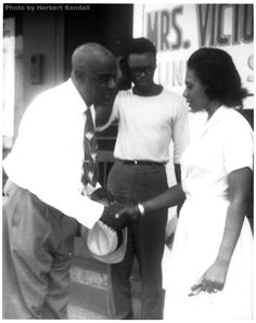 Three activists - one local, one professional, one volunteer - meet outside Freedom Summer headquarters at 507 Mobile Street: Reverend W.D. Ridgeway, pastor of True Light Baptist Church in Hattiesburg; SNCC Field Secretary Sandy Leigh (NYC), Dir Hattiesburg project; and Carolyn Reese (Detroit, school teacher), CO-Coordinator of the Hattiesburg project's Freedom Schools. EXCELLENT. Herbert Randall, USM archive