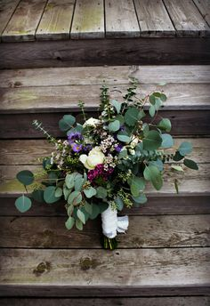 Bohemian, vintage and rustic styled fresh stem bouquet using eucalyptus, seeded eucalyptus, silver dollar eucalyptus, wax flower, purple and white asters, and vanilla ivory garden roses.