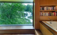 The spa-like bathroom in this Hudson Valley home has waterfall views and its own little library right above the tub.