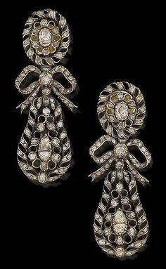A pair of 18th century diamond pendent earrings. Set throughout with rose and table-cut diamonds, each oval openwork surmount suspending a pear-shaped drop, with ribbon bow connector, all diamonds in silver closed-back settings, later post fittings, length 6.6cm.