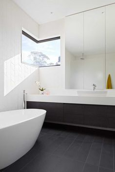 In this modern en-suite bathroom, a corner window adds natural light and provides a view of the trees, while dark flooring and a dark vanity contrast the white bathtub and white floor-to-ceiling tiles. Minimalist Bathroom Mirrors, Bathroom Mirror Design, Minimalist Bathroom Design, Bathroom Windows, Modern Bathroom, Bathroom Ideas, Bathroom Storage, Bathroom Interior, Bathroom Lighting