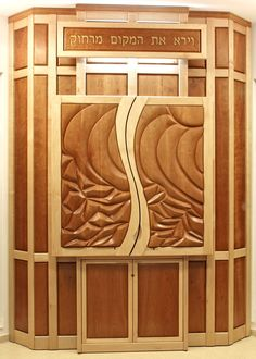 """Torah Ark (Aron Kodesh) """"Abraham Saw The Place From Afar"""" . Cherry and Maple wood. This synagogue furniture piece is made of columns of frame and raised panels, with the sculpted motif on the doors taking center stage."""