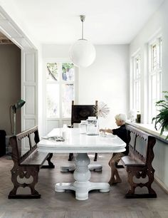 Bright Swedish dinning nook with a large white table, vintage wooden benches, and a mod pendant light