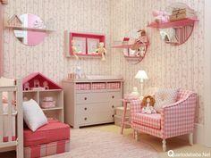 Poltrona de amamentação xadrez rosa com espelhos redondos na parede.